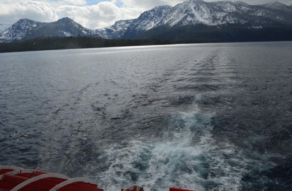 从船尾欣赏湖光山色,眼前微波荡漾,远处白云和雪山交相辉映。